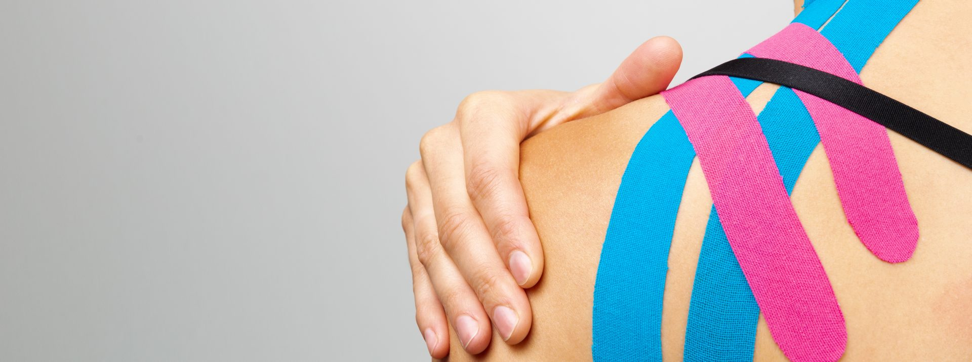 Woman with her hand on the shoulder testing the effect of Kinesio tape applied to her back by a physio